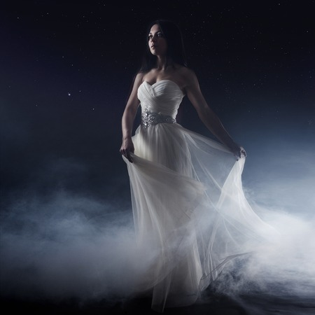 Portrait of girl in long white dress, mystical, mysterious style, dark background 免版税图像