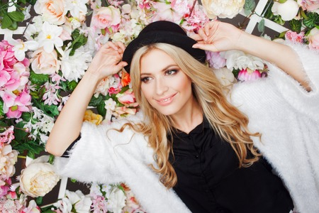 Young beautiful blonde woman in a fashionable hat on a floral background, Stock Photo