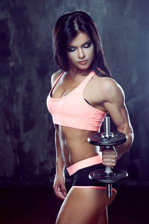 Young strong athlete posing on dark textured background