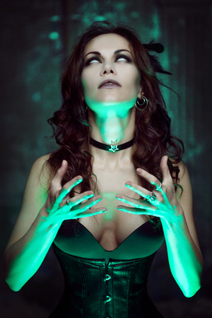 Halloween. Witch creates magic. Beautiful and sexy woman with a mystical light Stock Photo