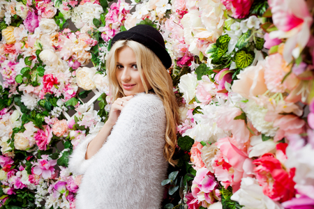 Young beautiful blonde woman in a fashionable hat on a floral background Stock Photo