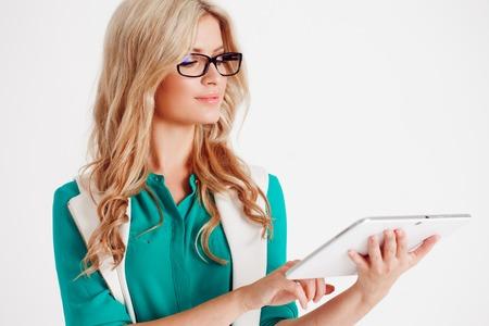 Retrato de la señora joven de negocios seguro, usar la tableta, el fondo blanco