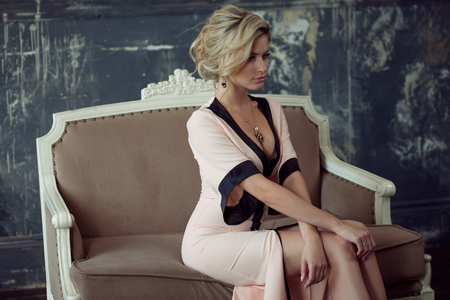 beauty girls: Fashion model with blond hair. Young attractive woman, siting on the sofa, vintage style
