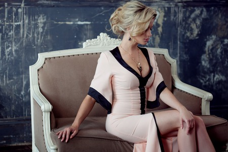 siting: Fashion model with blond hair. Young attractive woman, siting on the sofa, vintage style