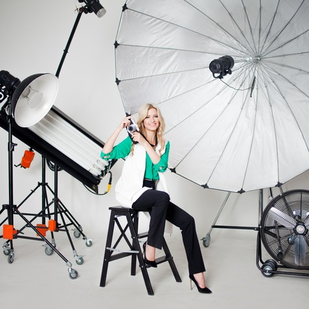 Girl photographer take a photo on the background of spotlights and technics for photostudios Stock Photo
