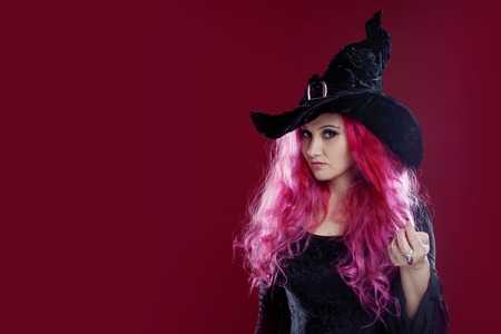 kinky: Attractive woman in witches hat and costume with red hair performs magic on a pink background. Halloween, horror theme. Stock Photo