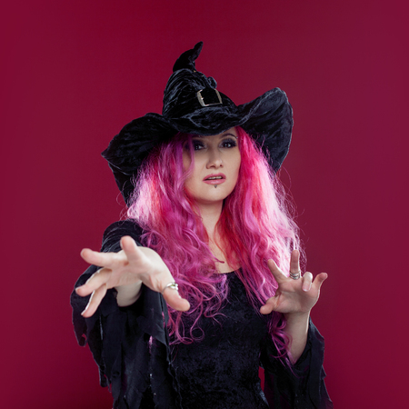 Attractive woman in witches hat and costume with red hair performs magic on a pink background. Halloween, horror theme. Stock Photo