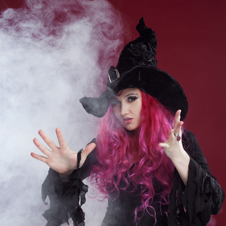 pointy hat: Attractive woman in witches hat and costume with red hair performs magic on a pink background. Halloween, horror theme. Stock Photo