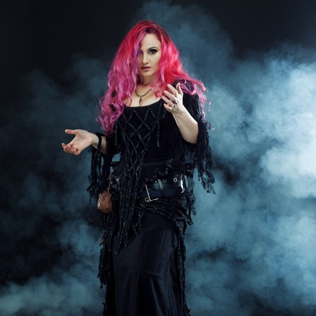 Halloween. Witch creates magic. Attractive woman with red hair in witches costume Stock Photo