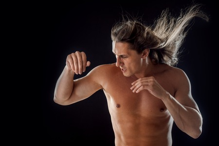 clasps: muscular man, clasps hands in fist, black background