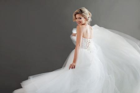 고급스러운 웨딩 드레스에 매력적인 젊은 신부. 흰색으로 예쁜 여자입니다. 행복, 웃음과 미소, 회색 배경의 감정 스톡 콘텐츠
