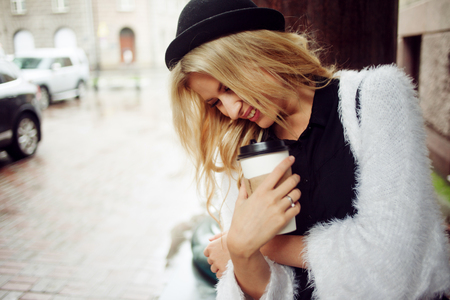Cheerful woman in the street drinking morning coffee
