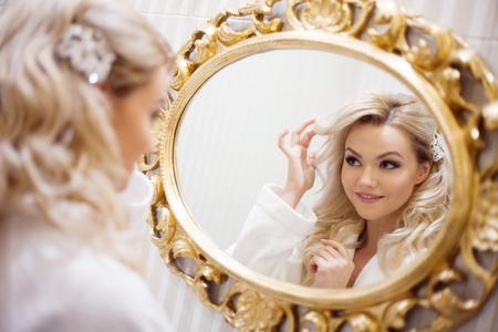 autocuidado: Retrato de la mujer atractiva joven vestido de blanco mirando el espejo. Foto de archivo