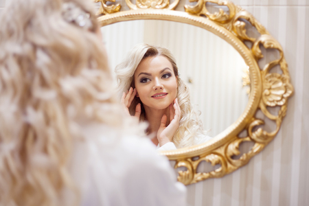 narcissism: Portrait of young sexy woman in white dress looking at the mirror. Stock Photo