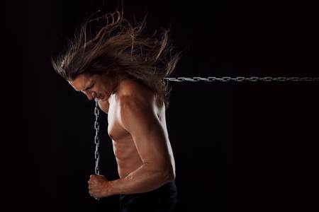 break chain: Young man with long hair dragging something behind him.