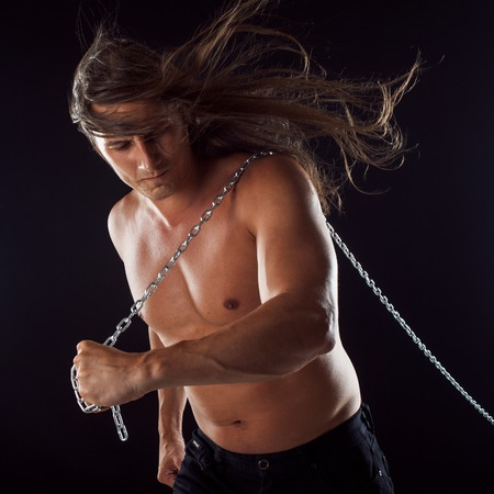 Young man with long hair dragging something behind him.