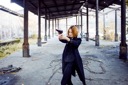 aiming: Woman pointing a gun. Girl shooting at someone on the street.