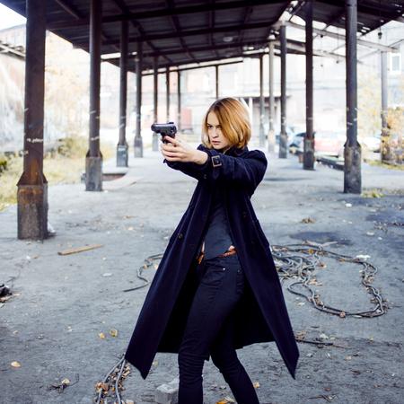 Vrouw die een pistool. Meisje schieten op iemand op straat.