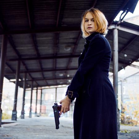 여자가 총을 가리키는. 길거리에서 누군가 촬영 소녀.