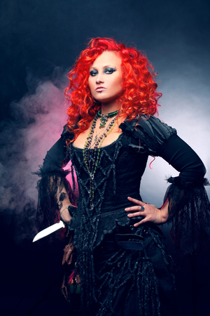 female shaman: Attractive woman with red hair in witches costume Stock Photo