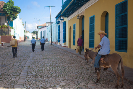 traditionally american: TRINIDAD, CUBA - NOVEMBER 9, 2012: Old man in the hat riding a donkey on the street