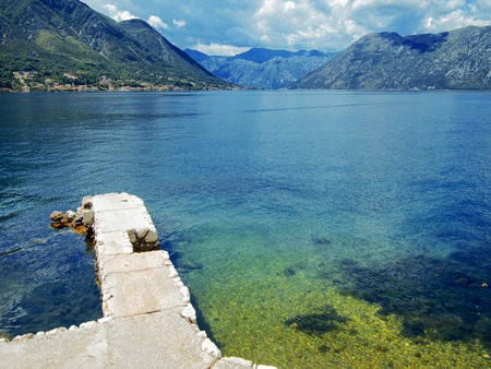 kotor: Seascape, pier stretching into the Bay, blue water