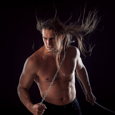 heaviness: Young man with long hair dragging something behind him.