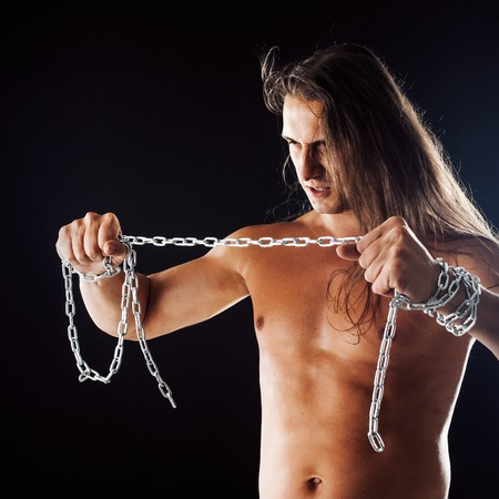 Young man with long hair breaks the iron chain