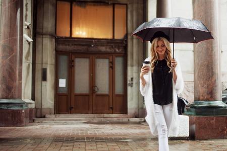 Cheerful woman under umbrella in the street drinking morning coffee. Walking girl