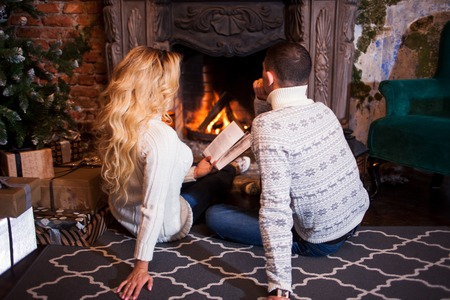 hearthside: Couple relaxing at home. Feet in wool socks near fireplace. Winter holiday concept