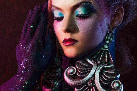 arrogancia: Young attractive blonde girl in a bright art-makeup, high hair, body painting. Rhinestones and glitter