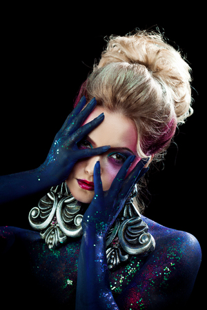 Young attractive blonde girl in a bright art-makeup, high hair, body painting. Rhinestones and glitter