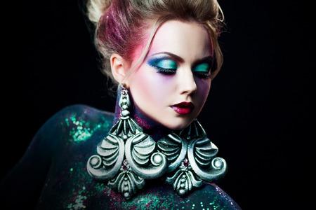 arrogancia: chica joven y atractiva rubia en un brillante arte de maquillaje, pelo alto, pintura corporal. Y brillantina