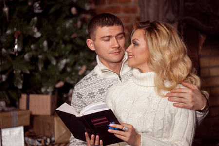 Man and woman in knitted sweater sitting on the floor by the fireplace Stock Photo