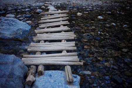 wooden makeshift bridge over a small river Stock Photo