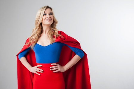 Superhero Woman. Young and beautiful blonde in image of superheroine in red Cape growing Фото со стока - 68660515