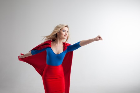 Superhero Woman. Young and beautiful blonde in image of superheroine in red Cape growing
