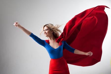 Superhero Vrouw. Jonge en mooie blonde in het imago van superheldin in het rood Cape groeien