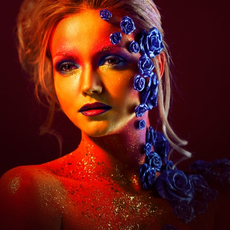 arrogancia: Portrait of young and attractive woman with art makeup. Fiery colors, glitter on face and floral decoration