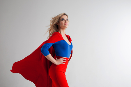 Superhero Woman. Young and beautiful blonde in image of superheroine in red Cape growing Фото со стока - 68746356