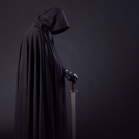 Portrait of a courageous warrior wanderer in a black cloak and sword in hand. Фото со стока - 68922502