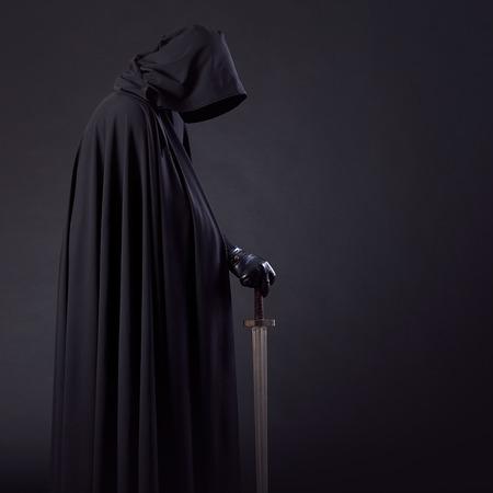 Portret odważnego wojownika wędrowca w czarnym płaszczu i mieczu w dłoni.