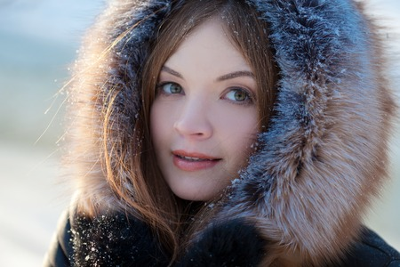 young and attractive woman in a coat with hood, close-up