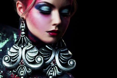 Young attractive blonde girl in bright art-makeup, high hair, body painting. Rhinestones and glitter