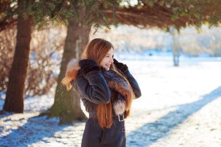 Young and attractive woman on walk, winter, warm coat with a hood