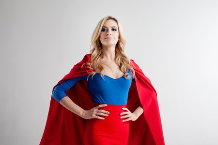 Superhero Woman. Young and beautiful blonde in image of superheroine in red Cape growing Фото со стока - 69543035