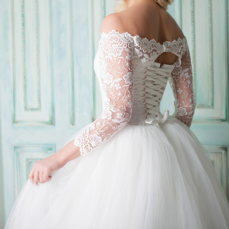 Portrait of charming woman in wedding dress. Dancing on the background walls with classic moldings