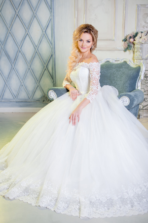 sits on a chair: Portrait of charming woman in wedding dress. The girl bride sits in a chair