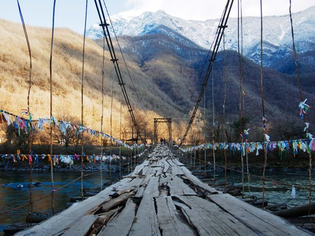 Old wooden bridge hanging over a gorge and mountain stream. Beautiful mountain landscape