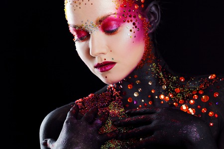 Young attractive girl in bright art-makeup, body painting. Touching lips Stock Photo